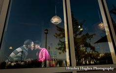 Romantic engagement portrait through a coffee house window by Heather Hughes Photography.