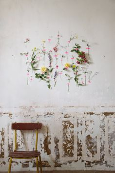 flowers attached to wall with washi tape....unusual wall decor using washi tape...be sure it doesn't damage wall.could do this on a piece of mat board or burlap or fabric covered bulletin and do tape embroidery on the board...Bebe'!!!