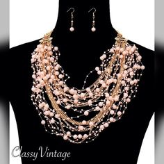 Elegant pink and gold layered necklace & earrings Gold tone chains, floating pink pearls on nylon cord and layers of chains make this a very elegant necklace. Matching pierced earrings. DaVinci Jewelry Necklaces