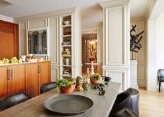 The handsome wood kitchen is open to the dining area, where a BDDW table takes center stage. Mid Century Armchair, Mid Century Dining, New York Apartments, Renovation Budget, Exclusive Homes, Alberto Giacometti, Custom Sofa, Gio Ponti, Upholstered Sofa