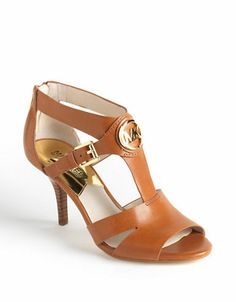 a58464984ecf4e Leather straps contrast with a shining designer logo on these Michael  Michael Kors pumps. Finished with a zippered back