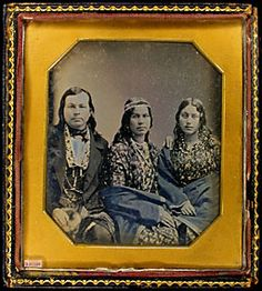 """Native-American Indians, man two women. Woman wearing necklace, earrings, headband. Pin prick gold tint. """"Uncle Andrew helped these Canadian Indians through school in Cayuga."""""""
