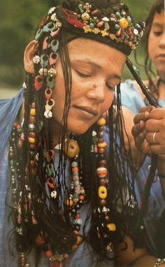 Africa |  Hair decoration is beloved by Mauritanian women. This fantastic example is out of Angela Fisher's Africa Adorned book.  Here her plaits are embellished with pendants, carved shell discs, triangular tailsmen, glass beads, carnelian and amber beads. | ©Carol Beckwith and Angela Fisher