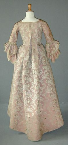 Robe a la Francaise, c 1760-70 pale pinky mauve shot silk tafetta brocade woven with a simulated lace meander alternating with large petalled flower sprays in white/silver thread.