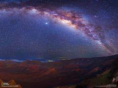 Fotografia di Wally Pacholka Velata di polvere interstellare, la Via Lattea si stende sopra il cratere del vulcano Haleakala nell'isola hawaiiana di Maui. Il panorama è il risultato dell'unione di tre fotografie.