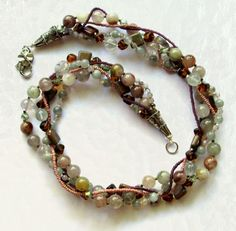 Maggies Beadery 22 inch three strand brown, Aquamarine and pink beaded necklace. This closes with sterling silver cones and a Tibetan Silver flower lobster clasp.