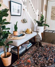 Love this stylish entryway! It has everything a welcoming, cozy entryway should - comfy sitting bench with storage underneath, gorgeous vintage rug, greenery & decor. Just lovely!