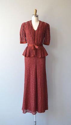 Vintage 1930s garnet bias cut sheer lace gown with gathered elevated bust, matching garnet slip, low cut square back, matching peplum jacket with puff shoulder short sleeves, single closure and silk trimmed cinched belt with bow. --- M E A S U R E M E N T S ---  fits like: xs/small  DRESS bust: 32-34 waist: 26 hip: 37 length: 54  JACKET shoulder: 15 waist: 26 length: 22 arm: 13  brand/maker: n/a condition: some wear to the silk at the jackets belt, see close up photo  to ensure...