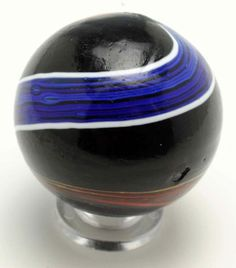 """Lot # : 254 - Large Indian Swirl Marble. Price Realized :   1,560.00 USD Precision banded Indian swirl. Black opaque base and a nice twist of precision bands. One band is blue bordered in white and the other band is red and yellow. Very hard-to-find in this size. Great surface condition except for one shallow chip. Condition (8.9). Size 1 - 5/16"""" Dia."""