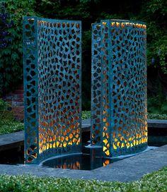 Three verdigris bronze Lattice water walls illuminated at night