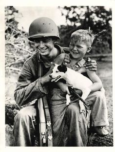 1942- U.S. soldier, a member of the U.S. 3rd Army on maneuvers in Louisiana, sits on a log holding his M-1 rifle, a small boy and the boy's dog.