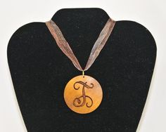 Monogram or Initial Necklace ($22) Wood disc engraved with your choice of monogram (curly or block) or single initial. Hangs from ribbon necklace.  Engravings Unlimited  To order email engrave9@gmail.com