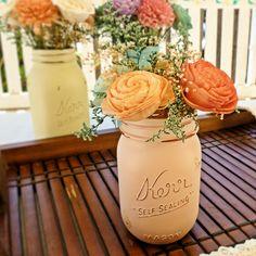 Pastel painted mason jars with floral arrangements for centerpieces.