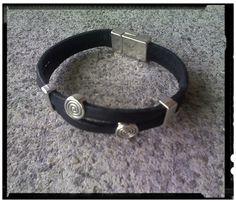 Pulsera doble cuero plano negro, con decoración círculos runa sin fin y cierre imán. En metal plateado.