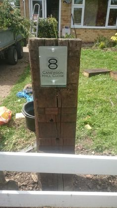 Reclaimed railway sleeper used as a post for a house number