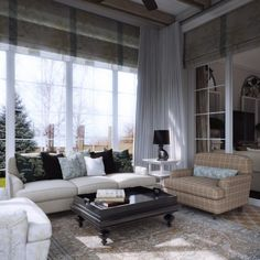 comfortable living area complete by cozy white sofa with cushions, brown sofa, a coffee table, unique table lamp and white curtain