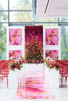 Brides.com: . Colorful ceremony altar with rose-covered flower wall and illustrated panels, created by Laura & Co Events.