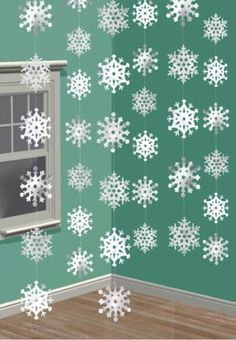DIY Tip: Cut out your own paper snowflakes to create cute garlands that hang from the ceiling.   Winter Wonderland Baby Shower   Image via Shindigz