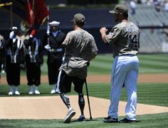 Game #87 7/8/12: Mark Kotsay #14 of the San Diego Padres walks with Marine Corps Cpl. Nick Kimmel before the first pitch in a baseball game between the San Diego Padres and the Cincinnati Reds at Petco Park on July 8, 2012 in San Diego, California. (Photo by Denis Poroy/Getty Images)