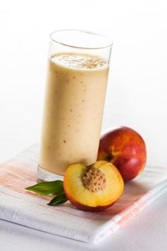 A clear glass filled with a peach color creamy thick peach smoothie.