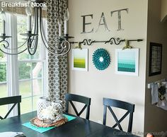 What a bright, sunny breakfast nook!  Love the wall decor with the curtain rod!