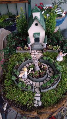 Miniature Fairy Garden - IN AWE. Two girl fairies who are IN AWE of the Blessed Mother and Baby statue at the Christian Village Church. One fairy kneels to give white flowers to the Blessed Mother; the other fairy is mesmerized by the experience. The church has a Cross at the top; tiny fuchsias are on each side of the vintage church. Succulents are used in the planters. It has the appearance of a English country garden with cemented stones around the statue and the vintage church.11/2015