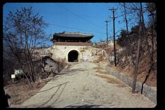 Seoul, North Gate, Dec 1966. Changuimun (창의문). The city wall is visible, especially on the right. The box under the arch is a residence. Photo by Stephen Dreher.