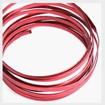 A coil of flat copper craft wire in red color