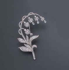 A DIAMOND LILY OF THE VALLEY BROOCH  Designed as a pavé-set diamond lily of the valley stem, extending similarly-set undulating leaves and articulated flowers, each with a circular-cut diamond accent and suspending a diamond briolette, mounted in 18k white gold.