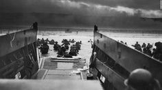 The Allies stormed the beaches of Normandy, France, on June 6, 1944. Here American troops hit the water from one of the landing craft. Soldiers on shore are lying flat under German machine gun fire.