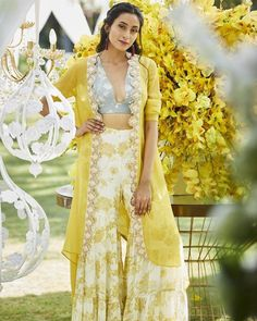 Varun-bahl Express style in your own way by wearing this floral embroidered & printed sharara with crop top & jacket. ,Floral embroidery ,Flared silhouette ,Comes with open jacket and crop top Indian Fashion Dresses, Dress Indian Style, Indian Designer Outfits, Designer Dresses, Indian Gowns, Pakistani Dresses, Indian Wedding Outfits, Bridal Outfits, Indian Outfits