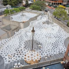 New York-based Jenny Sabin Studio has made a canopy of robotically knitted textile at MoMA PS1 in Queens that sprays mist in the day and glows at night.