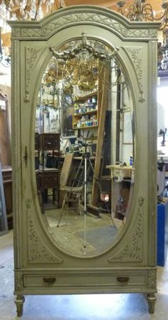 """""""A late 19th century French Directoire style, finely carved and antique green-painted single door Armoire, the door fitted with the original bevelled mirror"""""""