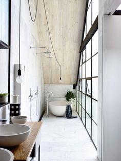 勾配天井の下の細長いバスルーム 2つのオーバーヘッドシャワー 1壁面はすべて格子入りの窓