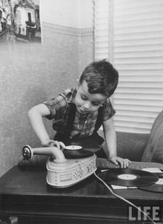 """vinylespassion:  Little boy listening to his records on a phonograph by Thomas D. McAvoy.  """