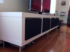 Speaker cloth wrapped doors attached with magnetic catches (easier than hinges): Ikea Lack shelf, Ikea Capita Legs, MDF, Acoustic Speaker Cloth, staples, cabinet magnets.