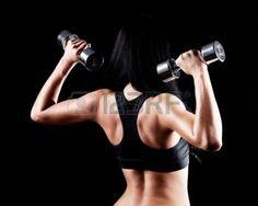 sportschool isolated: rug en handen van een jonge brunette sportieve gespierde vrouw uit te werken met twee metalen halters, geïsoleerd tegen zwarte achtergrond