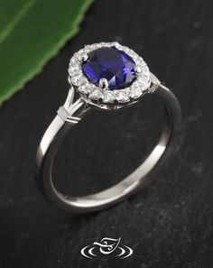 Beautiful Custom CAD/cast 950 palladium halo mounting with 4-prongs holding an oval cut blue sapphire in center.