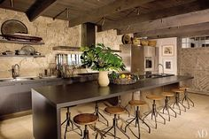 A stone wall, ceiling beams, and a barnlike door add rustic touches to the otherwise contemporary kitchen of a Malibu beach house designed by Michael Lee.