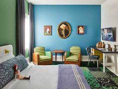 Quarto colorido tem móveis vintage, paredes azul e verde e tapete estampado
