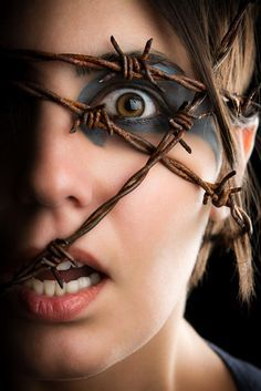 Creative headshot of terrified women with barbed wire wrapped around her head.