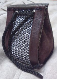 This awesome little guy is equipped with aluminum chain mail with brown and greed leather center and brown lambskin sides, handmade by yours truly. It measures about 9 cm (~3.5 inches) tall, 6 cm (2.5 inches) wide and 6.5 cm (~2.5 inches) long  This guy is perfect to hold dice, jewelry, change, or whatever your heart desires.