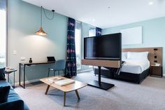 This modern hotel room has a television stand separating the bedroom space from the living space, while a desk is positioned against the wall under a single copper pendant light. #HotelRoom #InteriorDesign