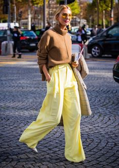 woman wearing yellow pants with a brown sweater