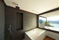 Stylish modern bathroom with black textured tiles, teak wood floors and lake view.