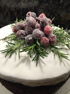 Round Christmas cake decorated with frosted cranberries and Rosemary.
