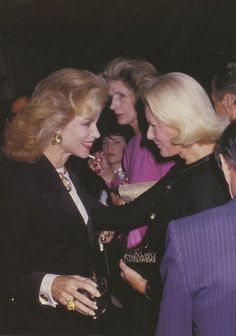 C.Z. Guest with Lynn Wyatt and Nancy Kissinger in the background at a Fete Famille III Benefit for AIDS Care Center at Mortimer's, 1988.  Photo by Ron Galella.