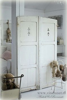 Vintage French Soul ~  Take some whitewashed, reclaimed shutters stenciled with a fleur de lis and make a special room divider or dress an empty space behind some beautiful pieces.