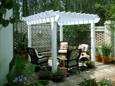 Outdoor Seating-Lush, tropical landscaping surrounds the outdoor seating area. A trellis provides partial shade from the sun.