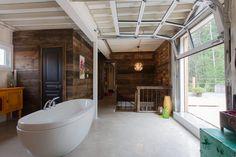 Utiliser une porte de garage à l'intérieur de sa maison pour s'en servir comme ouverture vers l'extérieur est une idée originale.